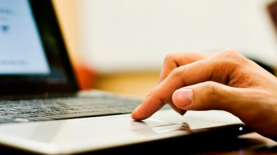 Hand of student with ADHD scrolling on laptop