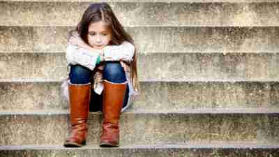 Girl with ADHD sitting on stone steps outside folding arms over knees