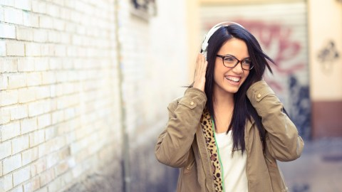 Young girl with ADHD with headphones in urban background