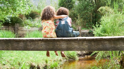 Girl with ADHD embracing boy with ADHD on footbridge over stream