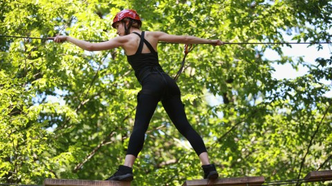 Young woman with ADHD climbing in adventure rope park