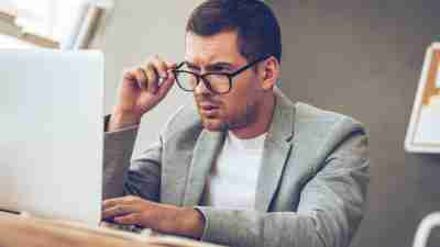 Man with ADHD looking confused at a laptop because for an accurate diagnosis you'll need a qualified clinician and a solid evaluation.