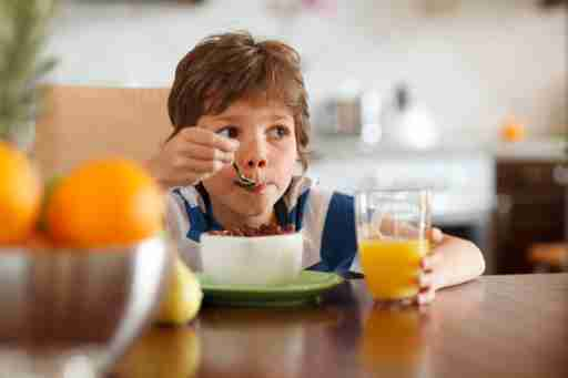 Cute boy with ADHD drinking orange juice and eating muesli for breakfast