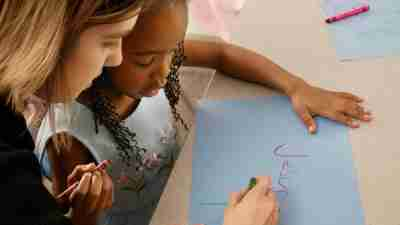 Woman helps child with symptoms of dysgraphia