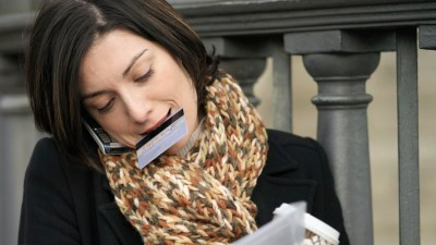 Woman trying to do too much, holding a credit card in her mouth and suffering on the phone