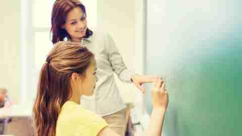 Girl with ADHD writing on chalkboard in school