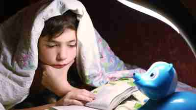 ADHD teen boy engaged in intriguing reading book under the blanket in night hour
