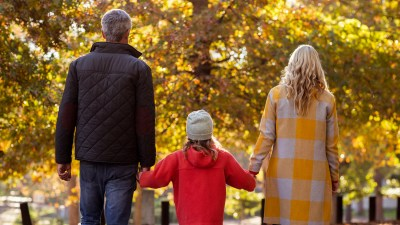 Rear view of ADHD girl standing with parents by trees on road at park
