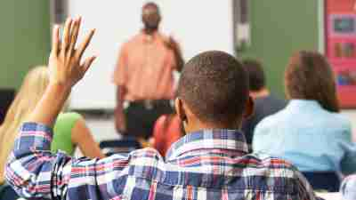 A teen with ADHD raising his hand in class, thinking about getting into college
