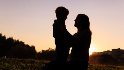 happy mother and little ADHD son at sunset