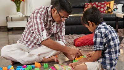 Father and ADHD son playing building blocks together