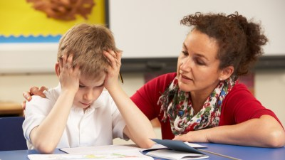 Stressed ADHD Schoolboy Studying In Classroom With Teacher