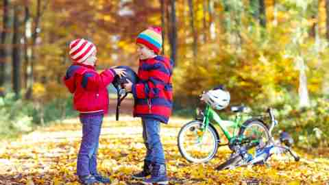 Two ADHD boys in autumn forest with bicycles.