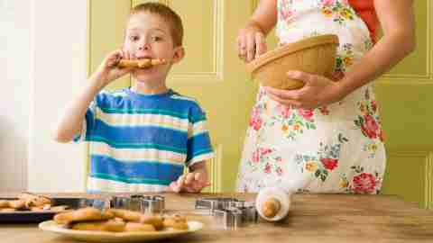 A boy standing up while eating a cookie; this behavior was how his parents knew he had ADHD