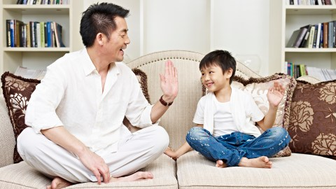 Father and son high-fiving after discussing his homework problems