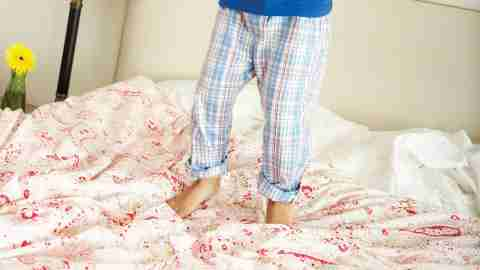 Children's feet, jumping on the bed, due to a lack of calm parenting strategies