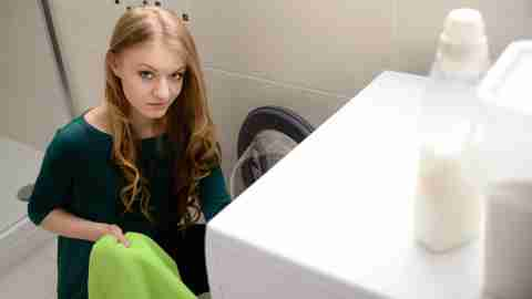 Teenage girl doing laundry with support from a parent