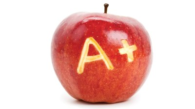 """An apple with """"A+"""" carved into it by a child happy to be changing school"""