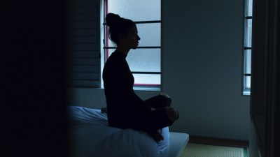 A woman sitting on a bed practicing meditation for ADHD