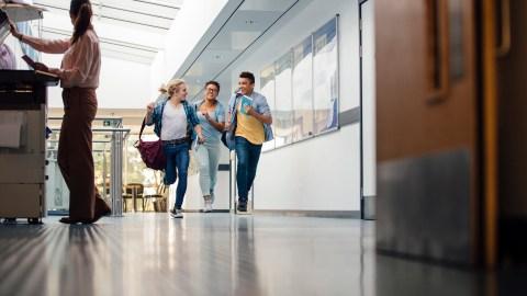 Teen students run down a school hallway