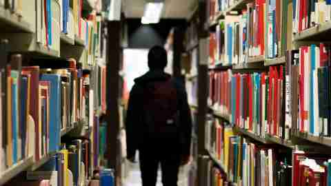 A teen with ADHD in the library, researching intrinsic motivation