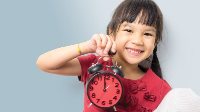 A young girl with ADHD holding a clock, smiling after a time-out that really worked