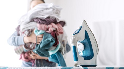 A woman with ADHD carries a huge pile of laundry to the ironing board.