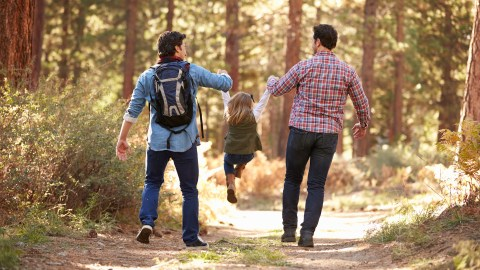 Two parents playing with their daughter in the woods; hands-on parenting skills are one of the benefits of loving someone with ADHD