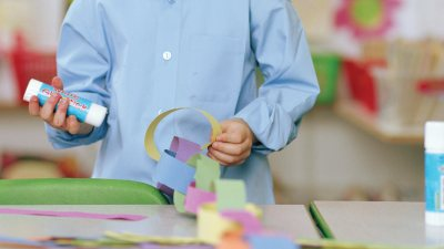 A child with ADHD doing crafts after being motivated by his teacher to try in class