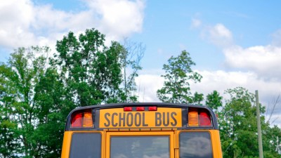 A school bus picks up students who are starting middle school.