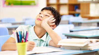 A child who rushes through his school work sitting at a desk and staring off into space