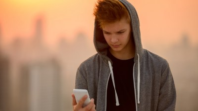 A teenage boy with no motivation looks at his phone outdoors.