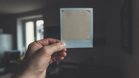 A mom with ADHD holds up a polaroid picture that sympbolizes her expecations for her children