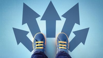 Teenage feet in sneakers, looking at arrows representing different ADHD treatment paths