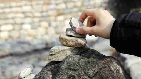 A woman laying stones on a larger rock, thinking about unfair ADHD parenting myths