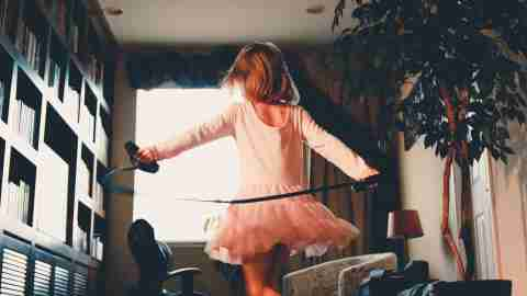 A daughter with ADHD runs around the house in a tutu with a jump rope.