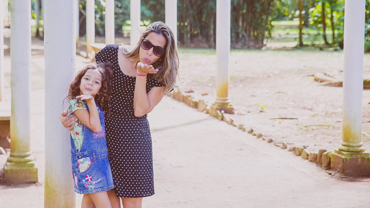 A mom and her daughter with ADHD blow a kiss to the camera