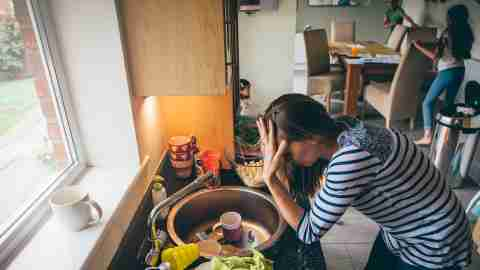 An ADHD mom at the sink is stressed while her kids run around the table.