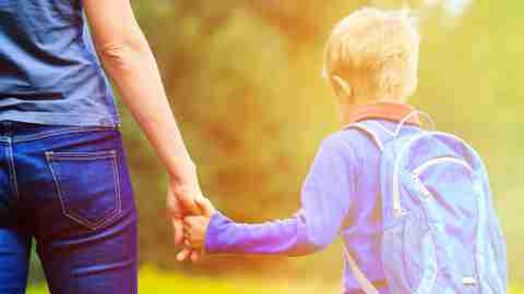 ADHD mom holding hand of little son with backpack outdoors, back to school