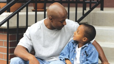 A father sitting on the steps with his child, telling him he has a learning disability