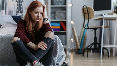 A young woman with social anxiety sitting on the floor of her room looking worried, not sure how to help herself