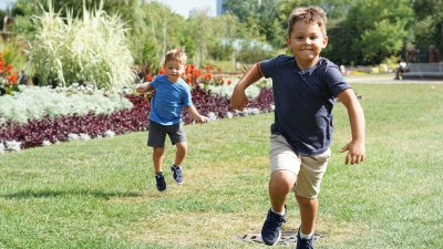 Two restless kids are running outside as part of their summer activities.