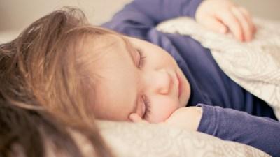 Sleeping child in purple pajamas