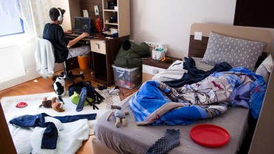 Teenager with a hoarding disorder is chatting on laptop in his untidy room