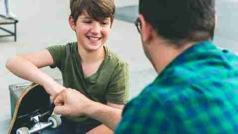 A dad fist bumps his teen son after helping him manage ADHD symptoms.