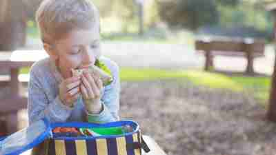 A boy struggles to finish his lunch after taking ADHD medication