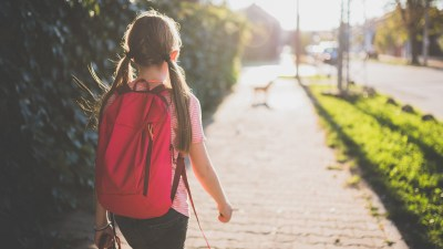 A girl with ADHD walks to school wearing a red backpack.