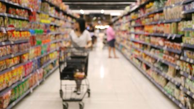 A woman grocery shopping ponders misconceptions about ADHD medication.