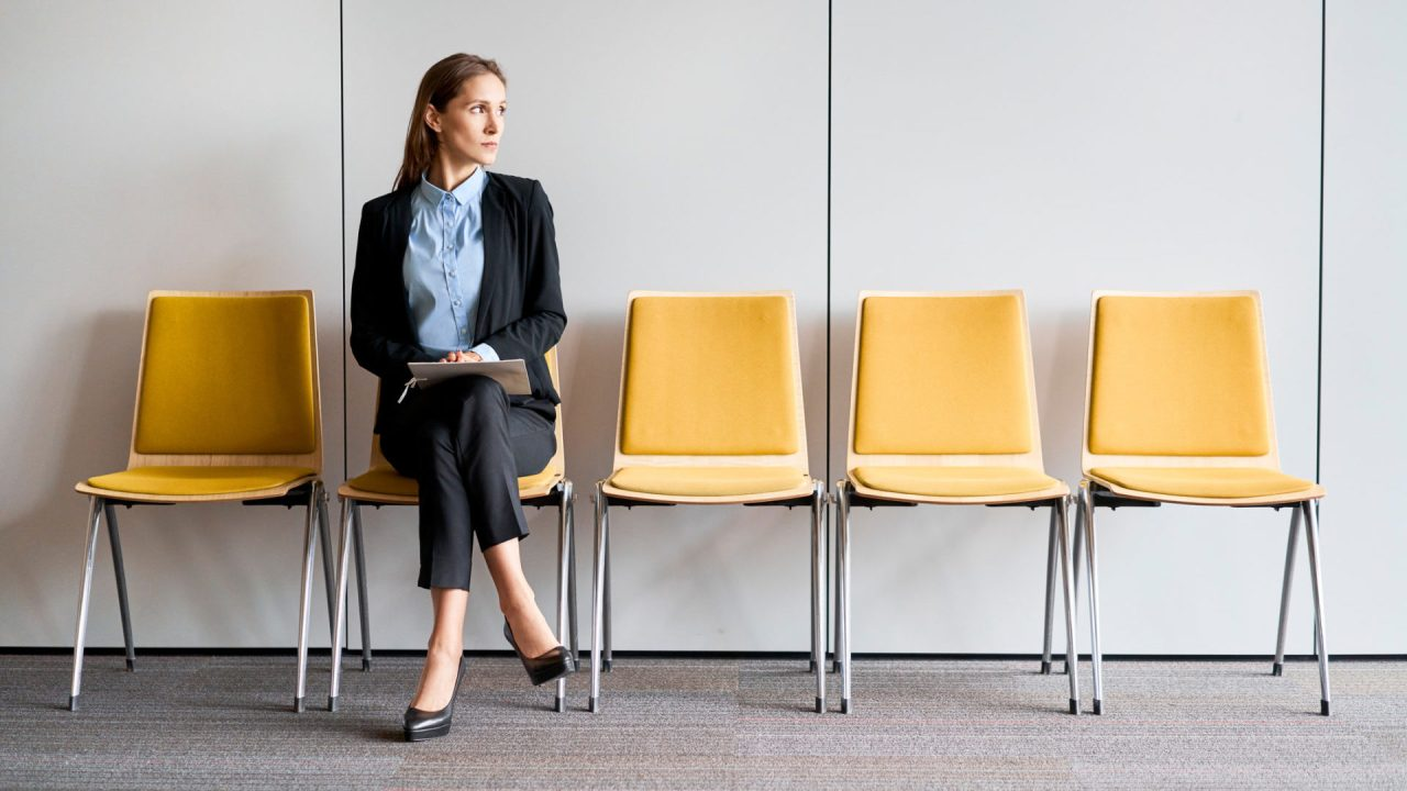 Young woman sitting in lobby with resume in hands and waiting for job interview