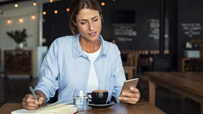 Mature woman sitting in cafe at table and typing a message on smartphone. Middle aged blogger making notes using organizing application on phone. Businesswoman reading information from smartphone while working remotely in cafe interior.